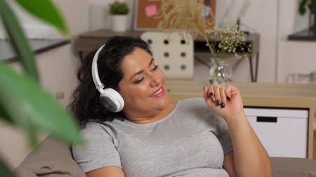 listening music : woman in headphones listens to music on smartphone Stock Footage