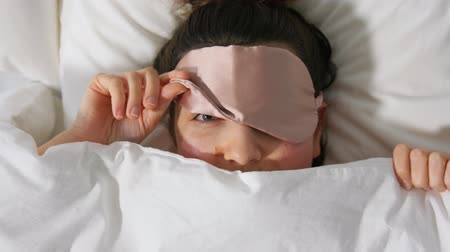 desperto : woman with eye sleeping mask in bed under blanket Stock Footage