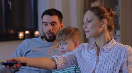 ispanico : happy family watching tv at home at night