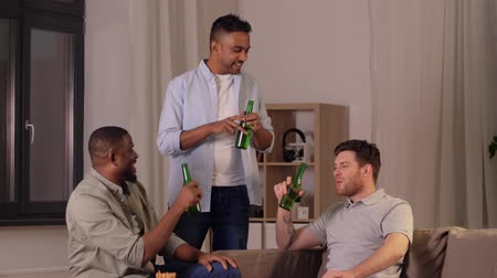 três pessoas : male friends drinking beer with crisps at home