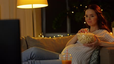 pregnant woman with popcorn watching tv at home Stock Footage