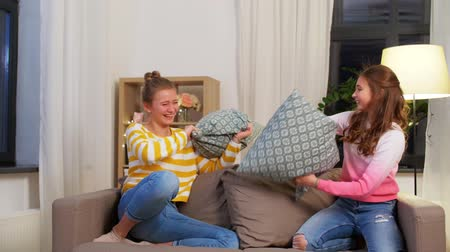happy teenage having pillows fight at home