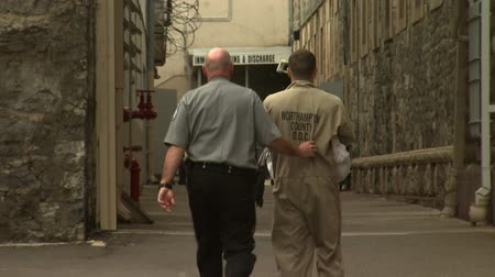 jailed : A Prison Guard Escorts a New Inmate Inside the Jailhouse