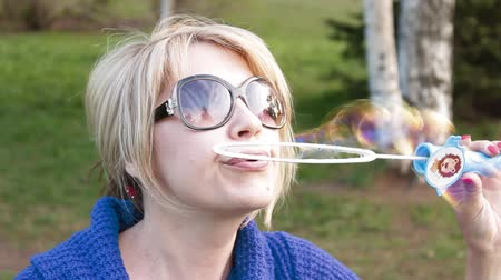 bańki mydlane : a beautiful woman blowing bubbles