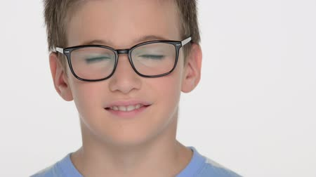 vizyon : Closeup portrait of the Pretty  boy of ten years, wears glasses, looks at the camera and smiles Stok Video
