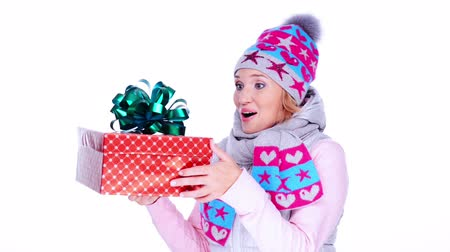 başörtüsü : Happy surprised adult woman with christmas gift in hands,  in a winter clothes posing at studio