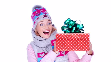рождество : Happy surprised adult woman with christmas gift in hands,  in a winter clothes posing at studio