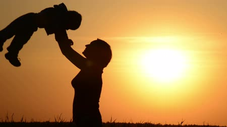 сумерки :  Happy mother plays with  baby at sunset