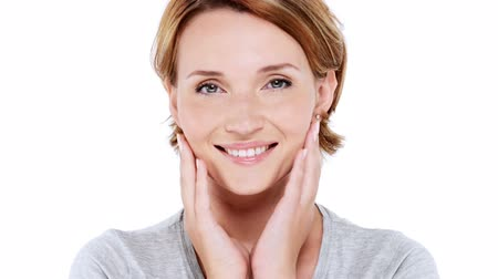 az emberi bőr : Beautiful smiling woman pampering skin of face over white background