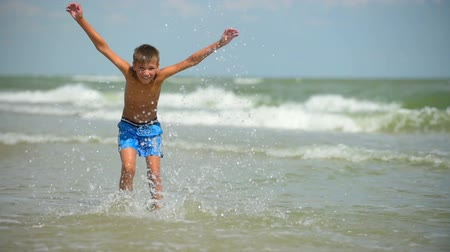 menino : Cheerful child of ten years splashing and plays in the sea.