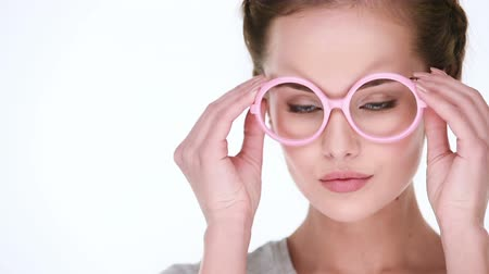 izgatott : Young beautiful smiling woman wears glasses pink and posing for the camera. Closeup view. Stock mozgókép