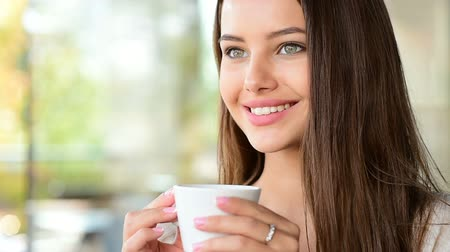 morning : Beautiful happy young woman drinks coffee at the cafe in the morning.