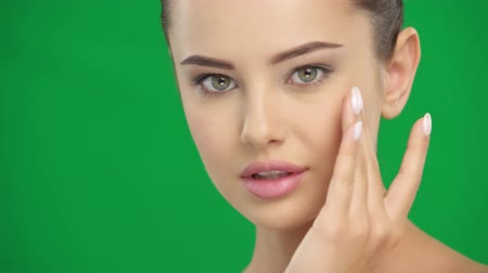 модель : Beauty face. Beautiful young woman pampering skin of face over  green screen. Portrait of cute and sexy girl with healthy skin. Beauty treatment concept. Стоковые видеозаписи