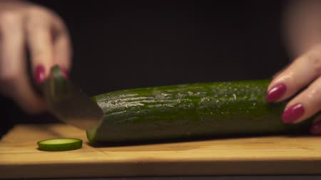 pepino : Girl cuts cucumber Clouse up