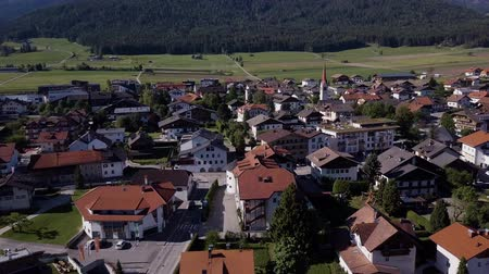 Aerial shot of traditional swiss village in Switzerland on a sunny day. Summer scenery of small town with view of houses on green grassy hills,majestic mountains in background under clear blue sky 動画素材