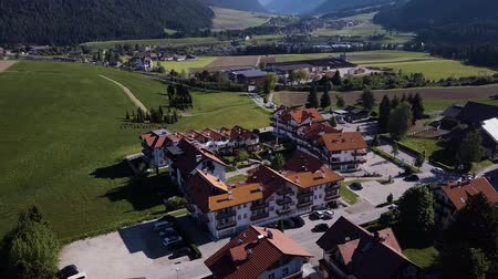 склон холма : Aerial shot of traditional swiss village in Switzerland on a sunny day. Summer scenery of small town with view of houses on green grassy hills,majestic mountains in background under clear blue sky Стоковые видеозаписи