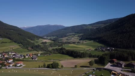 travnatý : Aerial shot of traditional swiss village in Switzerland on a sunny day. Summer scenery of small town with view of houses on green grassy hills,majestic mountains in background under clear blue sky Dostupné videozáznamy