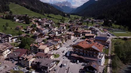 ekspres : Aerial shot of traditional swiss village in Switzerland on a sunny day. Summer scenery of small town with view of houses on green grassy hills,majestic mountains in background under clear blue sky Stok Video