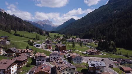 gramíneo : Aerial shot of traditional swiss village in Switzerland on a sunny day. Summer scenery of small town with view of houses on green grassy hills,majestic mountains in background under clear blue sky Vídeos