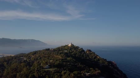 szmaragd : Aerial of a pretty village in Sardinia, Italy. Sunrise on the coast, mountains in the background Wideo