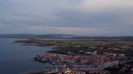 vnitrozemí : Aerial of a pretty village in Sardinia, Italy. Sunrise on the coast, parking yachts, mountains in the background