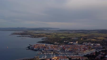 szmaragd : Aerial of a pretty village in Sardinia, Italy. Sunrise on the coast, parking yachts, mountains in the background