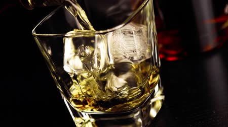 nightcap : close up pouring whiskey on bar table lounge bar atmosphere