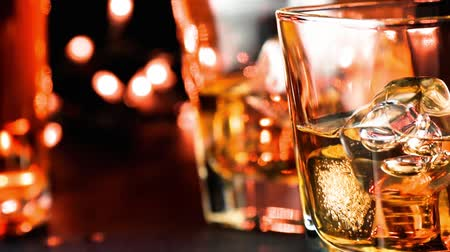 whisky : close-up versando whisky sul tavolo bar vicino bottiglie calda atmosfera