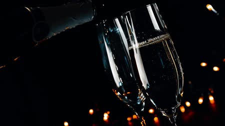na zdraví : barman pouring champagne into flutes with golden bubbles on black dark light background, christmas atmosphere Dostupné videozáznamy
