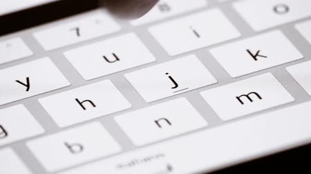 eszköz : Finger touching virtual keys form a digital keyboard of a touchscreen iPad tablet device.
