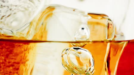 záběry : close-up of whiskey in glass with ice used for background, whisy texture