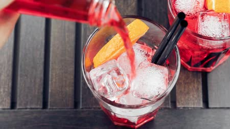 orange background : top of view of pouring red spritz aperitif aperol cocktail with orange slices and ice cubes on wood table