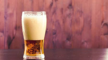 âmbar : pouring beer in glass with white foam on wood table background