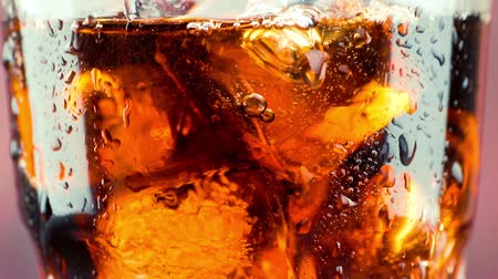 kola : close-up of pouring fresh coke with ice cubes, summer time concept