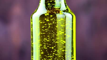 olivový olej : close-up of pouring olive oil in the bottle on wood background, concept of diet and nutrition