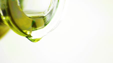 ramo : pouring olive oil with macro drops by bottle on brown white background, concept of diet and nutrition