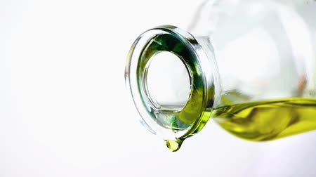 ramo : pouring olive oil with the bottle on white background, concept of diet and nutrition