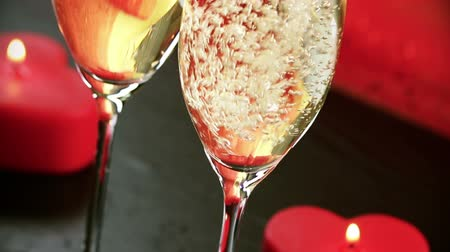 флейты : pouring champagne flutes near red candles burning, love and valentine day concept