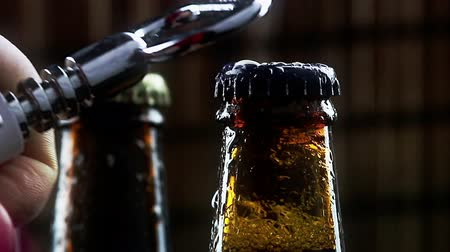 паб : man uncap three bottles of fresh beer with foam and drops on dark background pub, slow motion Стоковые видеозаписи