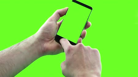 chroma key background : holding touchscreen device, close-up of male hand using a smart phone with chroma key, green screen on background, communication using smartphone technology concept Stock Footage
