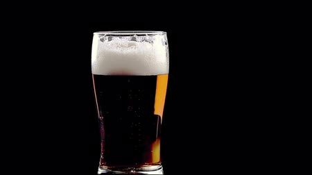 bögre : pouring fresh beer with foam into glass on black background