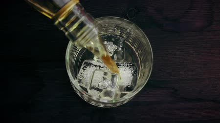 nightcap : barman pouring whiskey in the glass on wood table, view top, time of relax with whisky Stock Footage