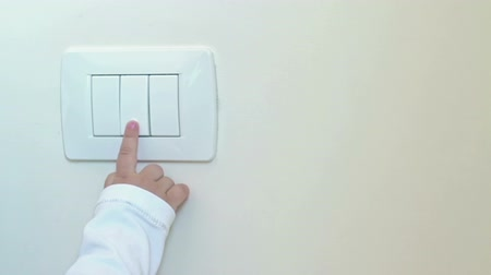 comutar : child little boy turning on the white light-switch with his finger of little hand, new generation concept