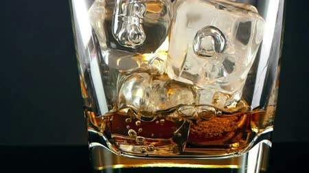 nightcap : Close-up of barman pouring whiskey in the drinking glass with ice cubes on black background, time of relax drink with whiskey, shot in slow motion Stock Footage