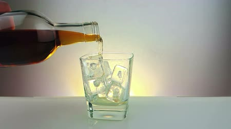 nightcap : Barman pouring whiskey with bottle in the drinking glass with ice cubes on warm white background, time of relax drink with whiskey, shot in slow motion