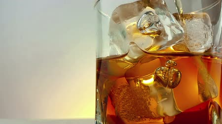 nightcap : Close-up of barman pouring whiskey in the drinking glass with ice cubes on warm white background, time of relax drink with whiskey, shot in slow motion