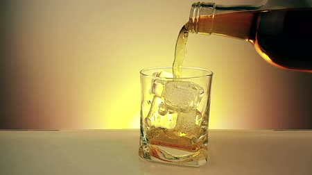 nightcap : Barman pouring whiskey with bottle in the drinking glass with ice cubes on warm gold background, time of relax drink with whiskey, shot in slow motion
