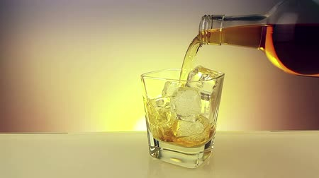 nightcap : barman pouring whiskey with bottle in the drinking glass with ice cubes on warm gold background, time of relax drink with whisky, shot in slow motion Stock Footage