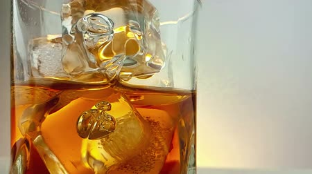 pálinka : close-up of  barman pouring whiskey in the drinking glass with ice cubes on warm white background, time of relax drink with whisky, shot in slow motion