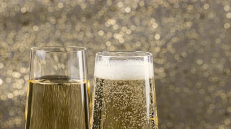 šampaňské : filling flutes of champagne with gold bubbles against gold bokeh background